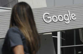 FILE - A woman walks below a Google sign on the campus in Mountain View, California, Sept. 24, 2019.