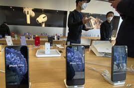 In this photo taken Wednesday, Feb. 19, 2020, staff chats with customers at an apple store in Beijing. Factories that make the…