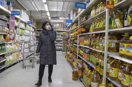 A shopper wearing a face mask browses an aisle of cooking oil in a supermarket in Beijing on Monday, March 16, 2020. China's…