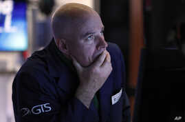 Specialist John O'Hara works at his post on the floor of the New York Stock Exchange, Thursday, March 12, 2020. The stock…