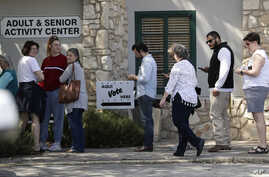 In this Friday, Feb. 28, 2020 photo, voters wait in line at an early polling site in San Antonio. California and Texas are the…