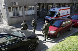 In this photo taken Monday, March 16, 2020, Serbian Army soldiers stand guard outside the Clinic for Infectious and Tropical…