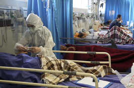 A medic treats a patient infected with the new coronavirus, at a hospital in Tehran, Iran, Sunday, March 8, 2020. With the…