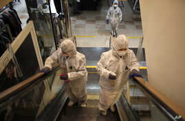 Workers wearing protective gear spray disinfectant as a precaution against the new coronavirus at a department store in Seoul,…