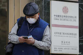 A man checks on his smartphone outside a stock brokerage that was closed except for limited transactions conducted through the…