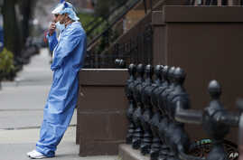 Wearing his personal protective equipment, emergency room nurse Brian Stephen leans against a stoop as he takes a break from…