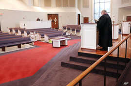 FILE - In this Sunday, March 15, 2020 photo, Rev. Kip Rush delivers his sermon in a sanctuary filled with mostly empty pews…