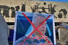 A poster with a defaced picture of Mustafa Kadhimi, Iraq's intelligence chief and new prime minister-designate, is shown in…