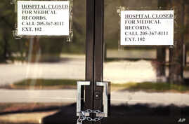 In this March 26, 2020, photo, closed signs hang on a recently closed Pickens County Medical Center in Carrollton, Ala. The…