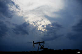 FILE - In this April 21, 2020 file photo, a pumpjack is pictured as a storm moves in  in Oklahoma City. Oil prices continue to…