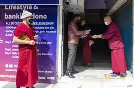 A bank employee standing in front of an ATM sprays sanitizer on a Tibetan Buddhist monk's palms to prevent the spread of…