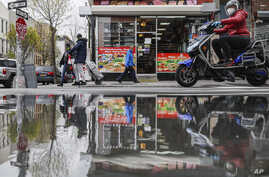 Pedestrians and motorists wear personal protective equipment as they pass a small grocery that is one of the few businesses…