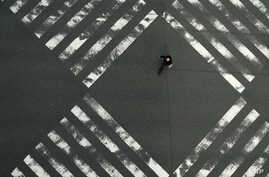 A woman walks through an empty pedestrian crossing in the Ginza shopping district Friday, April 3, 2020, in Tokyo. The new…