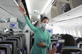 A flight attendant gives instructions to passengers on a plane in Ho Chi Minh City, Vietnam on Monday, March 16, 2020. The…