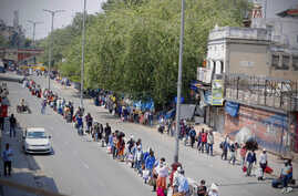 People line up to board trains outside New Delhi railway station in New Delhi, India, Tuesday, May 12, 2020. India is reopening…