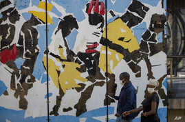 People wearing face masks as a precaution against the spread of the coronavirus, walks past a painting at a bus station in…