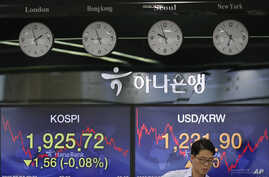 A currency trader works near the screens showing the Korea Composite Stock Price Index (KOSPI), left, and the foreign exchange…