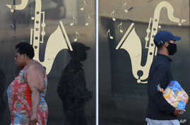 People walk past the window of a live jazz bar which has been closed during lockdown in Cape Town South Africa, Wednesday, May…