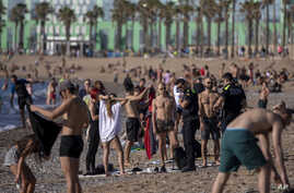 Police officers asks people to not sit while patrolling at the beach in Barcelona, Spain, Wednesday, May 20, 2020. Barcelona…
