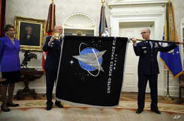 Chief of Space Operations at US Space Force Gen. John Raymond, center, and Chief Master Sgt. Roger Towberman, right, hold the…