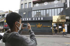 A man wearing a face mask takes pictures of a temporary closed dance club in Seoul, South Korea, Sunday, May 10, 2020. South…