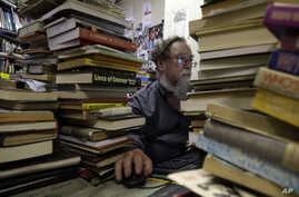 In this photo taken Monday, Feb. 8, 2016 Geoff Klass, works on a computer in his bookstore containing some 2 million books and…