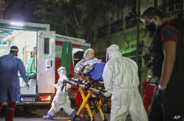 Health workers evacuate an elderly woman from a nursing home after residents of the facility tested positive for the new…