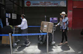 Stranded Australian citizens citizen stand in a queue to board a flight back to their country at Tribhuvan International…