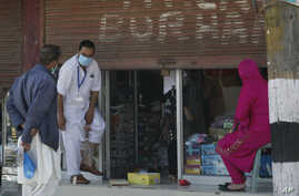 A Kashmiri man tries on a pair of shoes outside a shop, with it's shutters hald-closed, ahead of Eid al-Fitr during a…