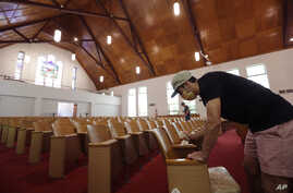 Alamo Heights Baptist Church pastor Bobby Contreras, right, works to clean, sanitize and prepare his church for services this…
