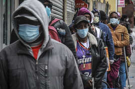 People wait for a distribution of masks and food from the Rev. Al Sharpton in the Harlem neighborhood of New York, after a new…