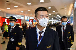 China Eastern Airlines flight crew wear protective masks on arrival at Sydney International Airport in Sydney, Australia,…