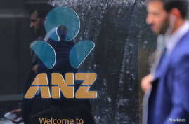 A pedestrian is reflected in the window of a branch of the Australia and New Zealand Banking Group (ANZ) in central Sydney,…