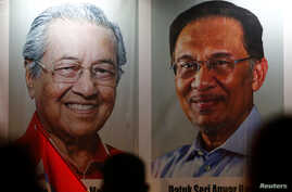 People pass posters of Malaysian Prime Minister Mahathir Mohammad and politician Anwar Ibrahim, who was granted a royal pardon,…