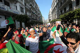 Demonstrators carry national flags as they march, a year since the start of weekly protests calling for a complete overhaul of…