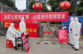 FILE PHOTO: Workers in protective suits are seen at a checkpoint for registration and body temperature measurement, at an…
