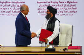 Mullah Abdul Ghani Baradar, the leader of the Taliban delegation, and Zalmay Khalilzad, U.S. envoy for peace in Afghanistan,…