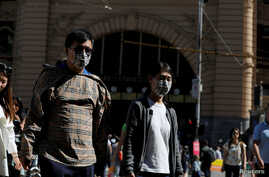 FILE PHOTO: People wearing face masks walk by Flinders Street Station after cases of the coronavirus were confirmed in…