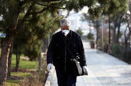FILE PHOTO: An Iranian man wears a protective mask against the coronavirus as he walks on a street in Tehran, Iran February 29,…