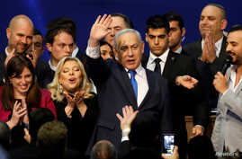 Israeli Prime Minister Benjamin Netanyahu stands next to his wife Sara as he waves to supporters following the announcement of…
