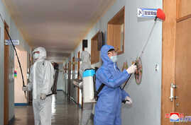 Volunteers carry out disinfection work during an anti-virus campaign in Pyongyang, North Korea in this image released by North…