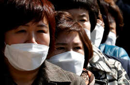 People wearing face masks stand in line to buy masks at a post office amid the rise in confirmed cases of coronavirus disease …