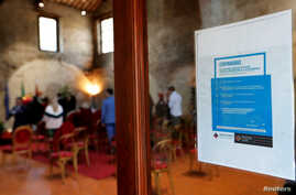 A health advisory poster is seen during a wedding ceremony with limited number of guests, standing one meter away from each…