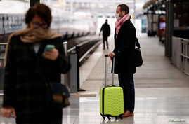 A man wearing a protective face mask waits for a train at Gare du Nord railway station in Paris after French President ordered…