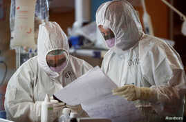 Medical workers in protective suits check a document as they treat patients suffering with coronavirus disease (COVID-19) in an…