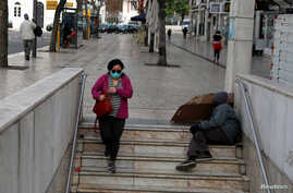 FILE PHOTO: A woman wearing a protective mask as a preventive measure against coronavirus disease (COVID-19) enters the subway…