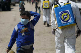 FILE PHOTO: An internally displaced Syrian girl wears a face mask as members of the Syrian Civil defence sanitize the Bab Al…