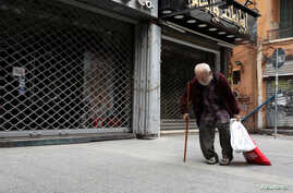 A homeless man walks past closed shops during a countrywide lockdown to combat the spread of the coronavirus disease (COVID-19)…