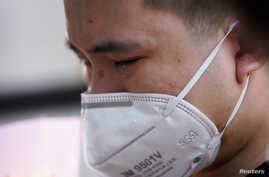 A man wearing a face mask cries in Wuhan, Hubei province, as China holds a national mourning for those who died of the…