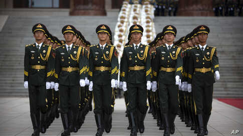 Honor guard members march before a welcome ceremony for Turkish President Recep Tayyip Erdogan at the Great Hall of the People in Beijing, China.